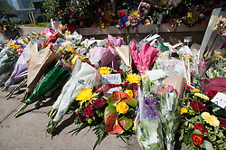 © London News Pictures. 26/05/2013. Woolwich, UK. Flowers (front middle) left by Rebecca Rigby, wife of Drummer Lee Rigby at the scene where he was murdered by two men in Woolwich town centre in what is being described as a terrorist attack. Photo credit: Ben Cawthra/LNP