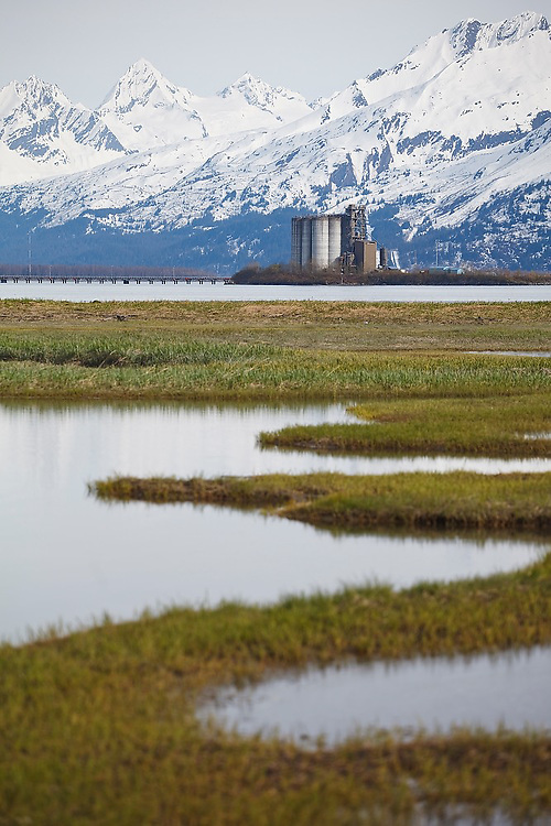 The Chugach Mountains rise above the Valdez Grain Terminal, built on an island in Port Valdez, Alaska.