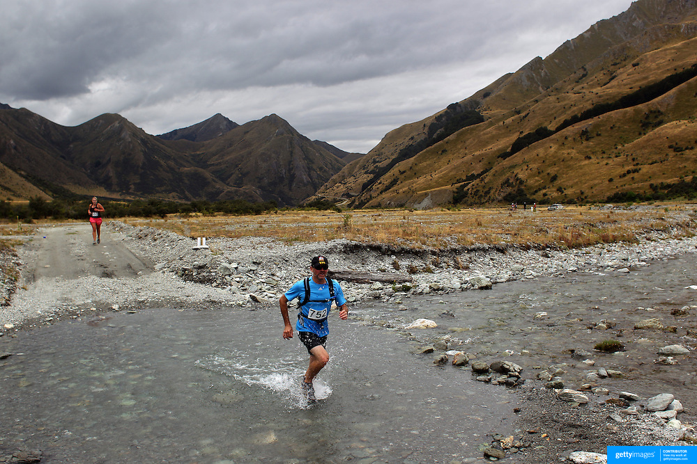 Runner Paddy Kilbride crosses Moke Creek on the Ben Lomond High Country Station during the Pure South Shotover Moonlight Mountain Marathon and trail runs. Moke Lake, Queenstown, New Zealand. 4th February 2012. Photo Tim Clayton