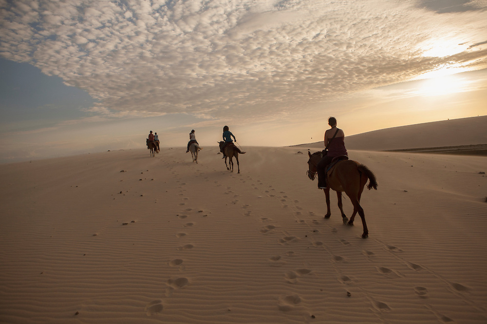 A group of people ride a horse at Jericoacoara dunes in Brazil.