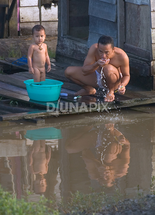 A Dayak and his toddler son living on Borneo's Mahakam River use dirty water to bathe and brush their teeth. According to the WHO, waterborne disease accounts for 4.1% of the annual global burden, and accounts for 1.8 million deaths annually.