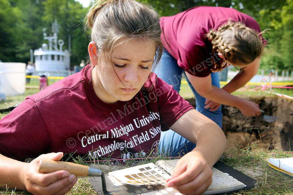 A student holds dirt next to a soil book which allows her to name the classification and group for the dirt during an archaeology dig at 40 Mile Point Lighthouse in Rogers City during the Central Michigan University Archaeology Field School photo by Emily Mesner