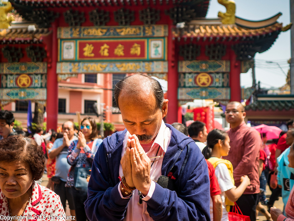 "08 FEBRUARY 2016 - BANGKOK, THAILAND: A man prays during Chinese New Year observances at Kuan Yim Shrine in Bangkok's Chinatown district, during the celebration of the Lunar New Year. Chinese New Year is also called Lunar New Year or Tet (in Vietnamese communities). This year is the ""Year of the Monkey."" Thailand has the largest overseas Chinese population in the world; about 14 percent of Thais are of Chinese ancestry and some Chinese holidays, especially Chinese New Year, are widely celebrated in Thailand.       PHOTO BY JACK KURTZ"