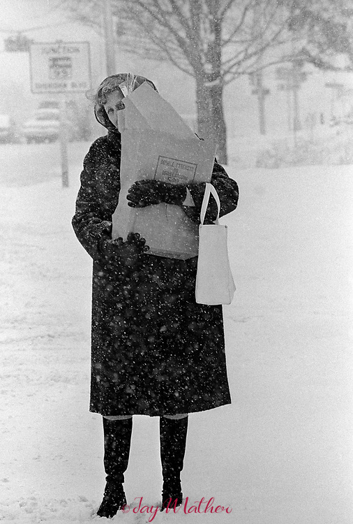 Woman with groceries at a bus stop at Dartmouth and Sheridan, March 1976.
