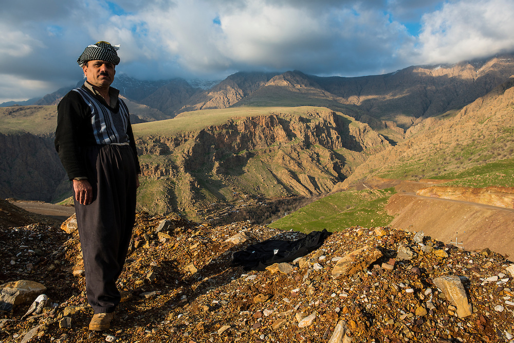 Traditional dressed Kurdish man before the mountain scenery of Ahmedawa on the border of Iran, Iraq Kurdistan