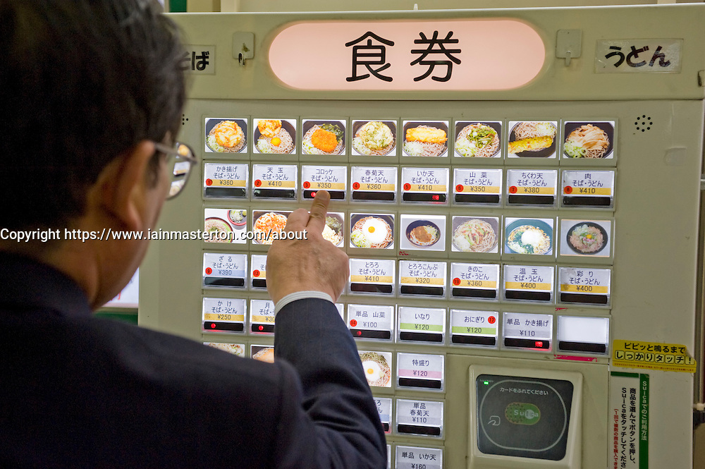 Man choosing meal from vending machine at a noodle restaurant in Tokyo Japan