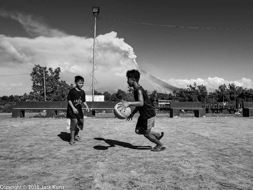 23 JANUARY 2018 - DARAGA, ALBAY, PHILIPPINES: Children play basketball while the Mayon volcano erupts in the background. Mayon is the most active volcano in the Philippines and its eruptions in January 2018 shut down most of Albay province and triggered the evacuation of almost 80,000 people.      PHOTO BY JACK KURTZ