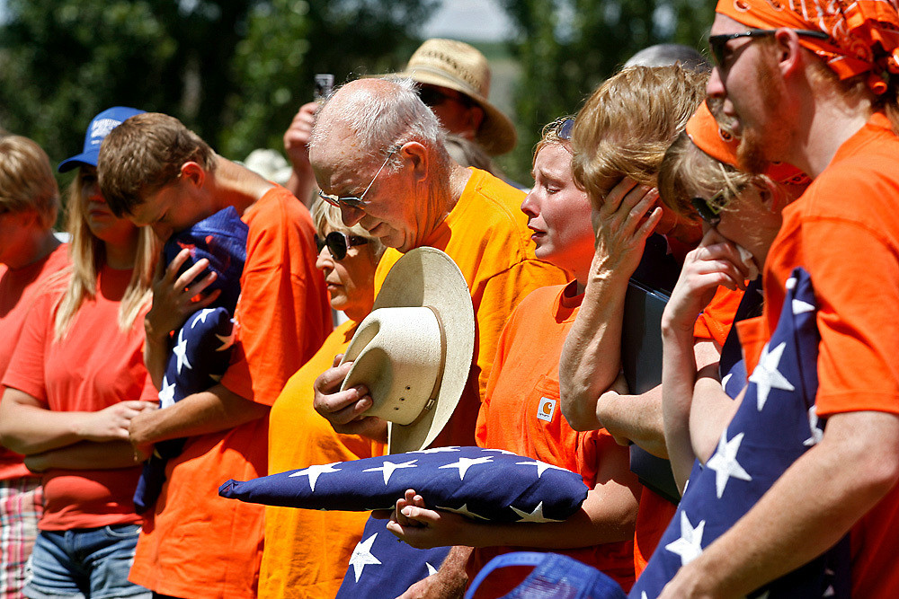 Chet Bauermeister's son Lester, left, stepmother Kathleen, father Don, daughter Amanda, wife Sandy, daughter Katelyn and son Josh listen to the final dispatch, relieving Bauermeister of his duty, Saturday during a memorial service following Basin City's Independence Day parade in 2010. More than 500 people gathered at Basin City Memorial Park to honor the fire chief, who died June 23 when his ATV flipped and rolled about 100 feet down a steep slope while he was helping to fight a brush fire. Mourners wore orange T-shirts in honor of Bauermeister, whom friends often kidded for wearing his trademark color.