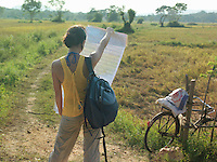 Young woman standing in fields holding map back view