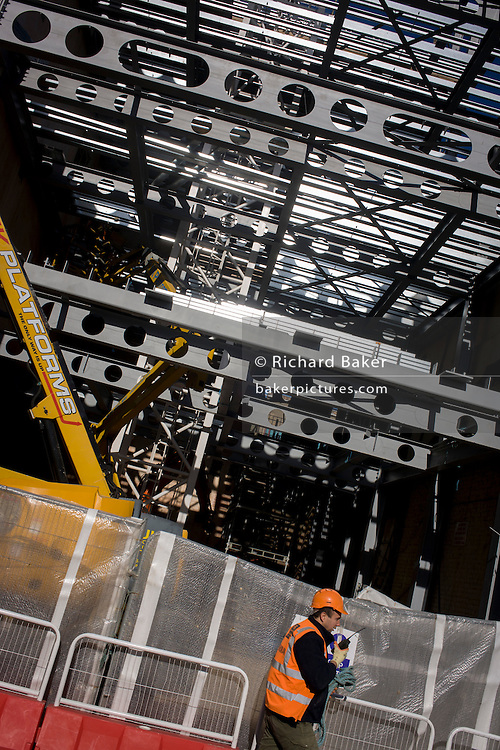 Highly-reflective steel girders shine in strong sunlight on a south London construction site.