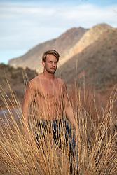shirtless blond man outdoors behind tall grass