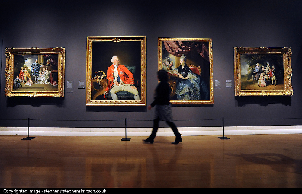 © Licensed to London News Pictures. 06/03/2012. London, UK. A woman walks past central portraits from the Royal Collection of George III and Queen Charlotte painted in 1771. Photo call for Johan Zoffany's portraits of George III and Queen Charlotte ahead of Johan Zoffany RA: Society Observed. The exhibition runs at the Royal Academy of Arts from March 10 to June 10 in Piccadilly, London. Photo credit : Photographer Stephen SImpson/LNP