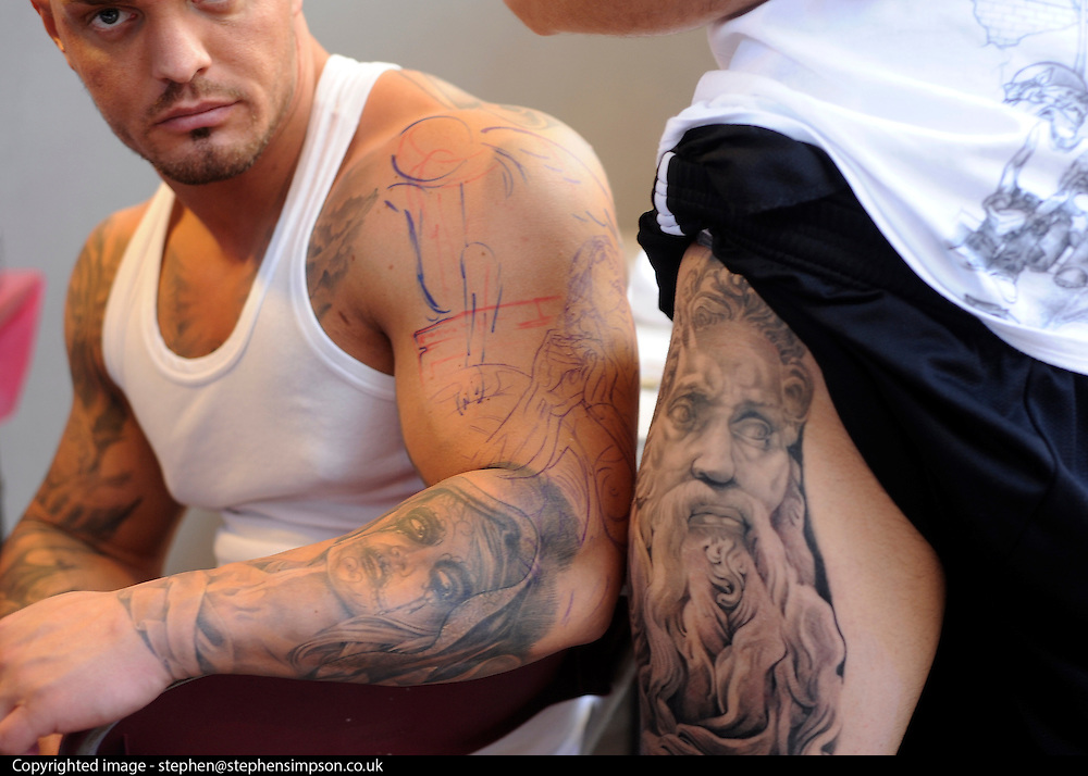 © Licensed to London News Pictures. 23/09/2011. LONDON, UK. Two men show off their tattoos. The 7th London Tattoo convention takes place today (23 Sept 2011) at the Tobacco Dock in the East End of London. The convention attracts artists and customers from all over the world. It runs until 25th September 2011. Photo credit:  Stephen Simpson/LNP