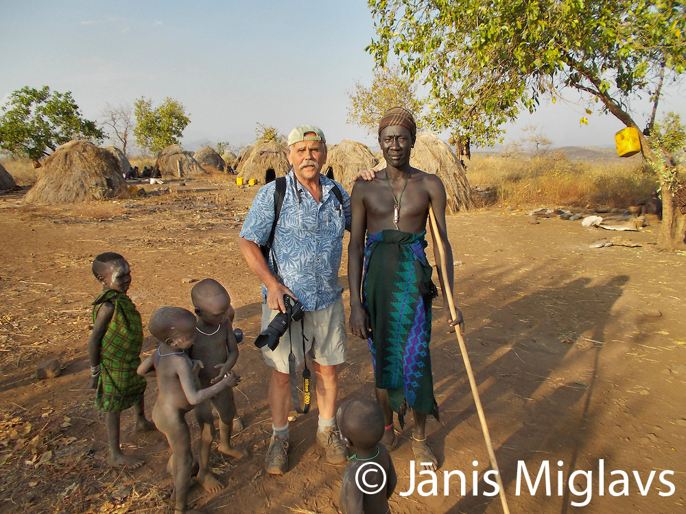 Photographer with warrior at Belle, a Mursi tribe village in Mago National Park, Omo Valley, Ethiopia, Africa.