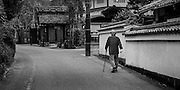 Old man walking back streets of Kyoto, Japan.