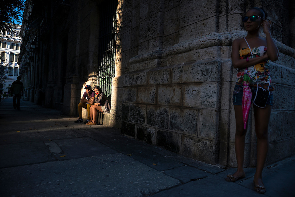 Josue, 18, and Lisandra, 25, sit on a ledge in sunlight off of Obispo Street near Plaza de Armas in Habana Vieja.
