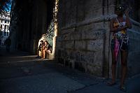 Josue, 18, and Lisandra, 25, sit on a ledge in sunlight off of Obispo Street near Plaza de Armas in Habana Vieja.