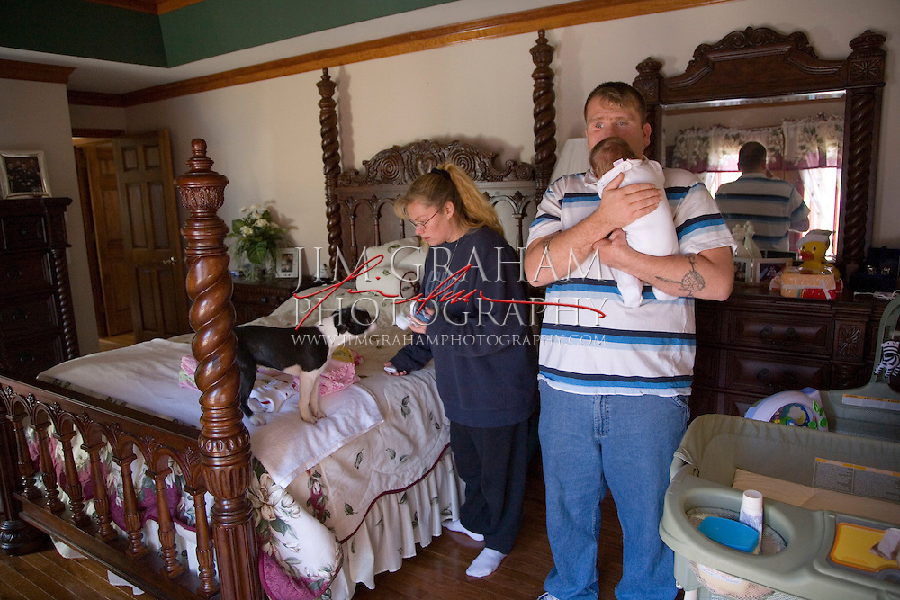 Jason Pepper gets ready to change a diaper for his daughter Cheyenne Noelle as his wife, Heather, sorts the laundry at their home in Primm Springs, TN., Monday Nov. 20, 2006. Photo by Jim Graham.