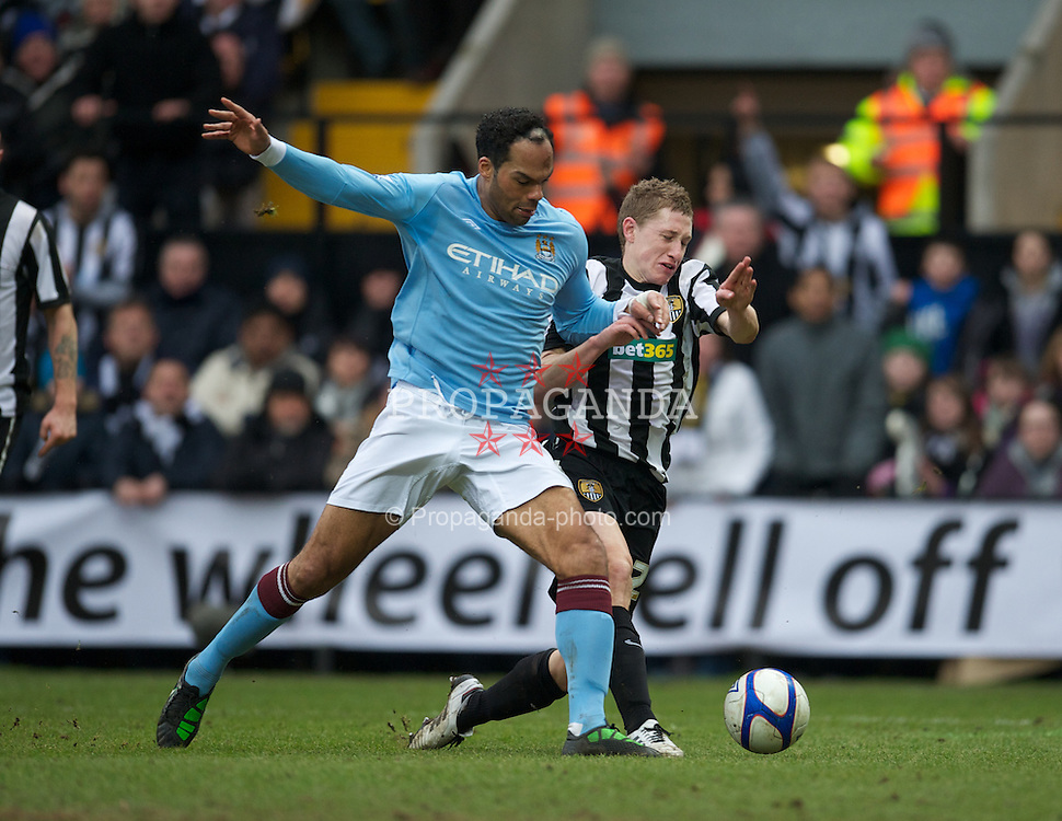 NOTTINGHAM, ENGLAND - Sunday, January 30, 2011: Manchester City's Joleon Lescott and Notts County's David Martin during the FA Cup 4th Round match at Meadow Lane. (Photo by David Rawcliffe/Propaganda)
