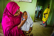 The Shagari Primary Health Clinic in Gusau Nigeria offer prenatal care.    Here Shafa Aliyu Galadima and her three year old daughter, Fatima Ahmed wait for medical attention.