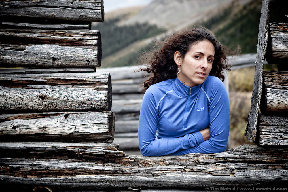 A latina woman in the wind in the ruins of a ghost town log cabin in Colorado.