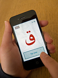 Student learning Arabic using educational app on an Apple iphone 4G smartphone