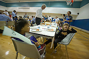 Washington, DC. (October 15, 2010) -- Fathers and kids of the River School celebrate their Friday afternoon with a Dad's hot lunch bunch in the school gym.  The River School provides successful educational experiences for children and their families by uniting the best practices of early childhood education and oral deaf education, and to promote clinical research and training in child language and literacy. The River School is located in Northwest, Washington, DC.  Photo by Johnny Bivera