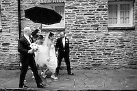 The bride is tended to as a groomsman carries her bouquet and shelters her with an umbrella and two bridesmaids tend to her train.