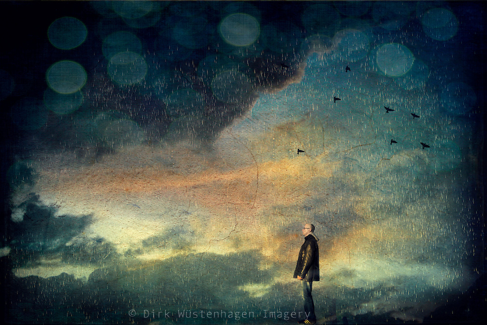 Man standing in a rain shower under a dramatic sky