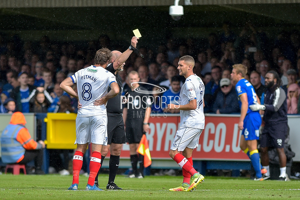 Portsmouth Midfielder, Stuart O'Keefe (7) shown a yellow card during the EFL Sky Bet League 1 match between AFC Wimbledon and Portsmouth at the Cherry Red Records Stadium, Kingston, England on 9 September 2017. Photo by Adam Rivers.