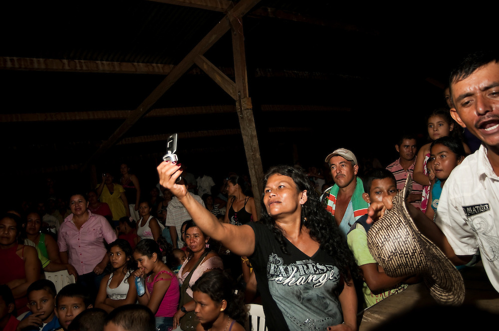 A fan takes a photo with a cell phone of narco-ballads singer, Uriel Henao during a concert in El Retorno, Colombia. Henao sings about drug trafficking, guerrillas and their impact on the civilian population.  Narco-ballads are controversial, and are largely banned from mainstream radio stations, yet are widely popular in small towns in rural Colombia.
