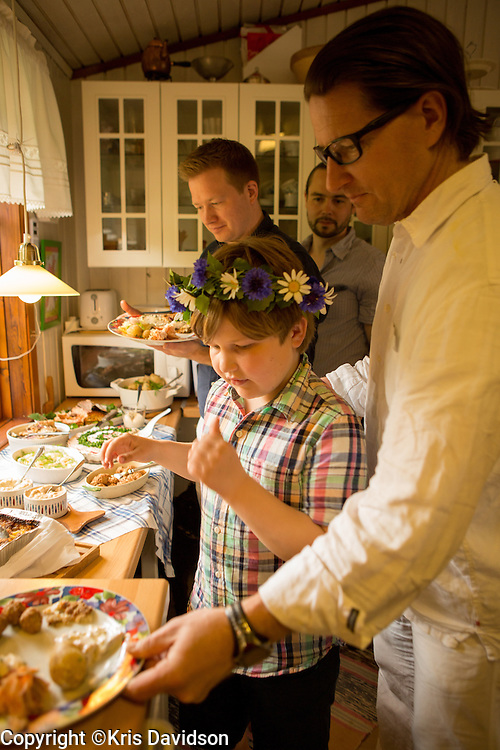 Boy fills his plate with traditional Swedish fare during the Midsummer holiday on Öland, a Swedish island in the Baltic Sea. The longest day of the year is a beloved holiday in Sweden; the cities are empty as the locals take to the countryside for a day of dancing and singing with family and friends.