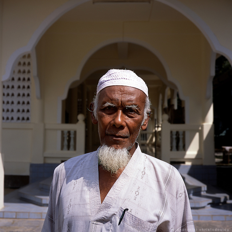The local imam in frond of the mosque where he serves, in Karbi village. .Karbi village is a small mushlim village near the border with Malaysia. The main production of the village is rubber.