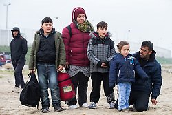 © Licensed to London News Pictures . 24/10/2016 . Calais , France . A Kurdish family of mother , father and three children aged 11 , ten and four years old respectively , leaving the Jungle migrant camp in Calais , Northern France , with their parents , on the day of a planned eviction and start of the destruction of the camp . Photo credit: Joel Goodman/LNP