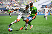 New England Revolution midfielder Gustavo Buo (7) moves the ball past Seattle Sounders defender Xavier Arreaga (25) during a MLS soccer game, Saturday, Aug. 10, 2019, in Seattle.  The teams played to a 3-3 tie. (Alika Jenner/Image of Sport)