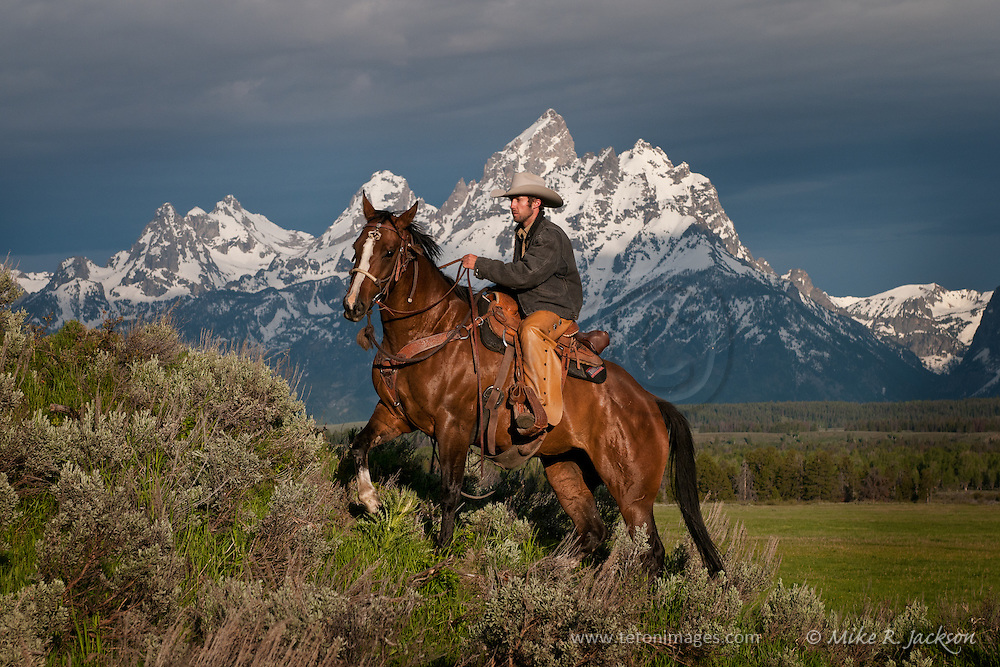 Wrangler and horse climbing a steep hill in front of the Grand Teton mountain range in Jackson Hole, WY
