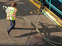 A female ferry line handler stows a line on departure from Bremerton in Rich Passage of Puget Sound, Washington, USA