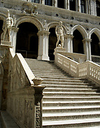 Interior courtyard, facade of the Doge's Palace in Venice, Italy. The palace was the residence of the Doge of Venice, the supreme authority of the Republic of Venice. Its two most visible façades look towards the Venetian Lagoon and St. Mark's Square, or rather the Piazzetta. The use of arcading in the lower stories produces an interesting 'gravity-defying' effect. There is also effective use of colour contrasts. largely constructed from 1309 to 1424, designed perhaps by Filippo Calendario. It replaced earlier fortified buildings of which relatively little is known. Giovanni and Bartolomeo Bon created the Porta della Carta in 1442, a monumental late-gothic gate on the Piazzetta side of the palace. This gate leads to a central courtyard. The palace was badly damaged by a fire on December 20, 1577.