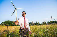 An African American man holding a small model of a wind turbine. Concept of green energy / green business