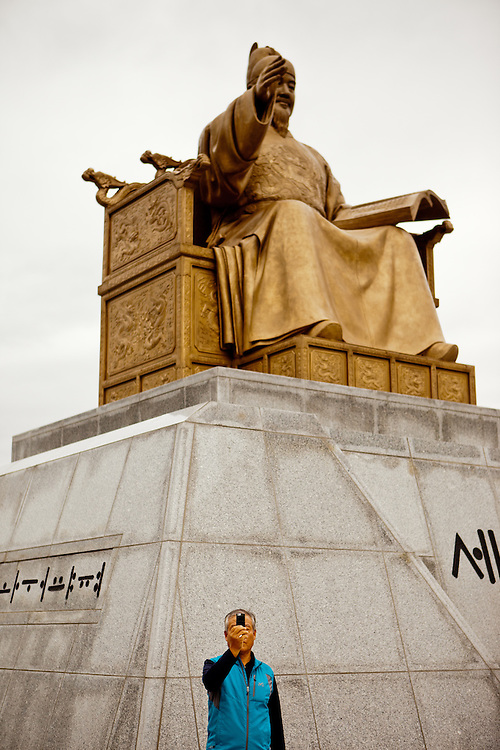 Man doing a selfportrait with his mobile phone at the statue of King Sejong in Gwanghwamun Square during the Chuseok national holiday in the city center of the Korean capital Seoul.