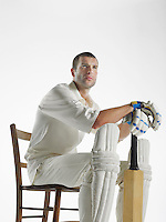 Cricket player sitting in chair holding cricket bat side view