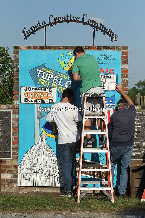Aycock, McNeal and Jerry Duckett install the mural on April 19 at the community garden on Spring Street in Tupelo.