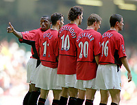 Eric Djemba-Djemba (Utd) lines up the United wall for a free kick. Manchester United v Arsenal. Community Shield.10/8/03. Millennium Stadium. Credit : Colorsport/Andrew Cowie.