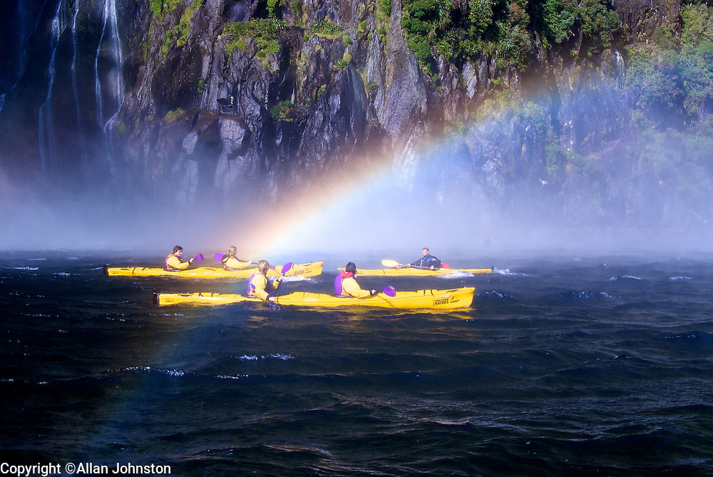 Sea Kayaks chasing Rainbows in Milford Sound  World Heritage area Fiordland National Park New Zealand.<br /> Sea Kayaks chasing Rainbows in Fiordland National Park, New Zealand. People in Kayaks kayaking, Queenstown, Roscos. Milford Track NZ