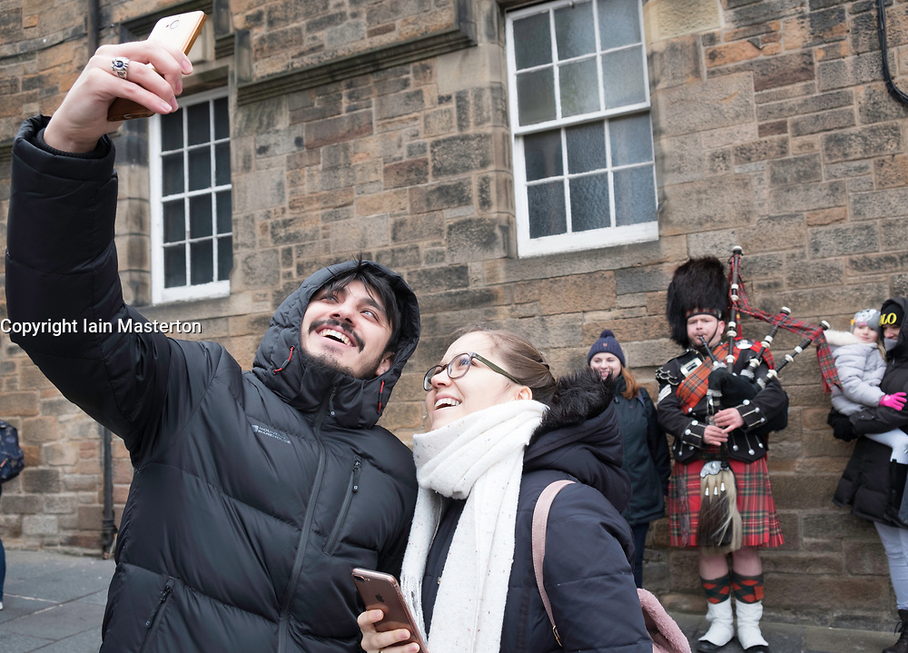 Tourists taking selfie with piper busking on The Royal Mile, Edinburgh Old Town, Scotland, United Kingdom