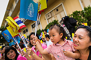 "01 AUGUST 2013 - BANGKOK, THAILAND: A Thai woman and her daughter wave the yellow flag of the monarchy while they chant ""Long Live the King"" at Siriraj Hospital before Bhumibol Adulyadej, the King of Thailand, 85, was discharged from Bangkok's Siriraj Hospital, Thursday where he has lived since September 2009. He traveled to his residence in the seaside town of Hua Hin, about two hours drive south of Bangkok, with his wife, 80-year-old Queen Sirikit, who has also been treated in the hospital for a year.      PHOTO BY JACK KURTZ"