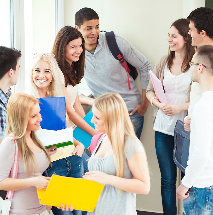 Multi-ethnic group of college students talking in the hallway.