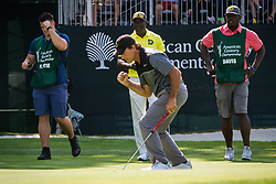 July 15, 2018 - Stateline, Nevada, U.S - Heisman Trophy winner and former NFL quarterback, DOUG FLUTIE, reacts to his successful put on the 17th green at the 29th annual American Century Championship at the Edgewood Tahoe Golf Course at Lake Tahoe, Stateline, Nevada, on Sunday, July 15, 2018. Flutie's caddy, former NFL running back, TERRELL DAVIS, and Davis' caddy look on. (Credit Image: © Tracy Barbutes via ZUMA Wire)