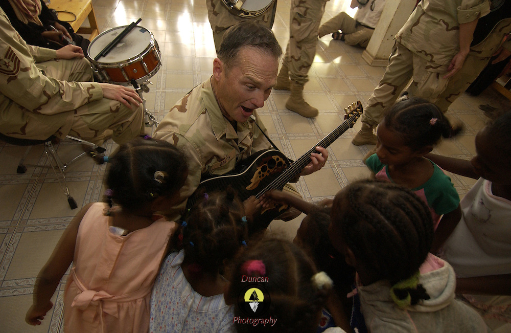 DJIBOUTI CITY, Djibouti -- June 16, 2006 -- U.S. Air Force Master Sgt. James Bristow plays with children at Aicha Bogoreh Center for the Protection of Mothers and Children, an orphanage housing 160 girls up to age 21. The U.S. Air Force Academy Band joined a group of U.S. Military members based at Camp Lemonier, Djibouti on a visit to the orphanage.
