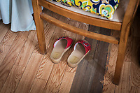 VERBANIA, ITALY - 18 APRIL 2017: Emma Morano's home sandals are seen here under a chair by her bed in her small room in Verbania, Italy, on April 18th 2017.<br /> <br /> Emma Morano, born in 1899, was an Italian supercentenarian who, prior to her death at the age of 117 years and 137 days, was the world's oldest living person whose age had been verified, and the last living person to have been verified as being born in the 1800s. She died on April 15th 2017.